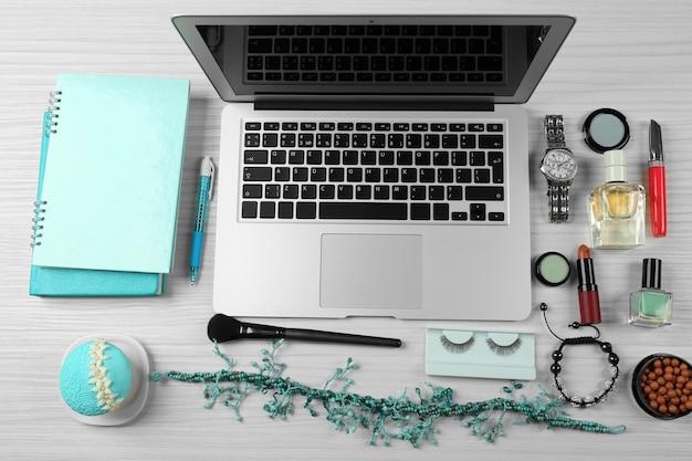 Laptop com acessórios femininos na mesa de madeira branca