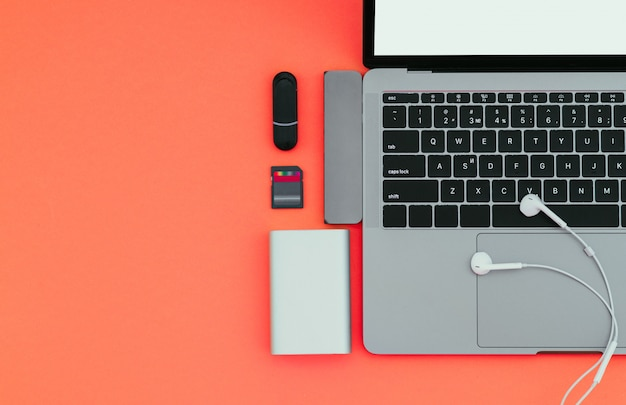 Laptop com adaptador usb tipo c, pen drives, fones de ouvido e banco de potência em uma superfície vermelha