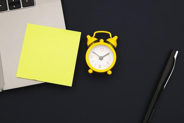 Laptop com adesivo, espaço para texto, alarme amarelo e caneta em um azul escuro.