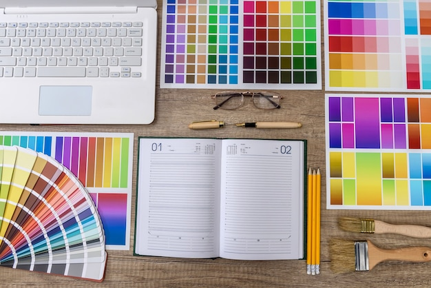 Laptop com amostras de cores na mesa de madeira para reforma residencial
