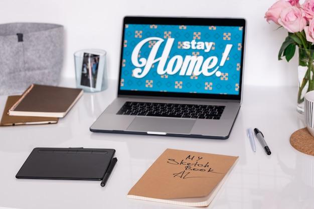 Laptop com anúncio de ficar em casa em exibição, bloco com caneta, caderno, canetas, cadernos e rosas no local de trabalho do designer