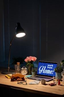 Laptop com anúncio de trabalho em casa em exibição, caderno, lanche e bebida, flores e despertador com lâmpada sobre os suprimentos no quarto escuro