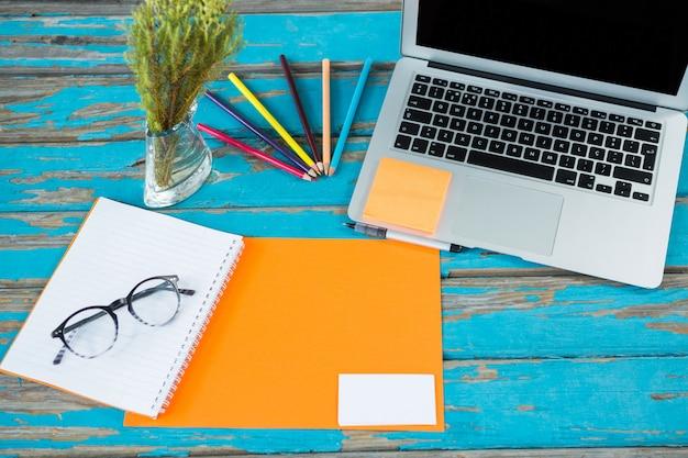 Laptop com arquivo, caderno espiral e espetáculo