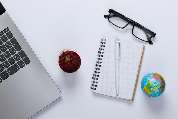 Laptop com cacto, caderno, globo em um branco. espaço de trabalho minimalista
