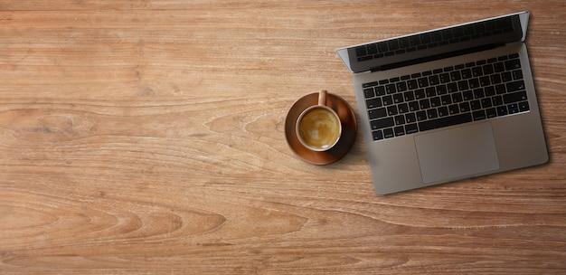 Laptop com café na mesa de madeira. faixa panorâmica