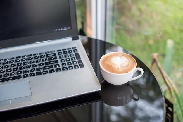 Laptop com café quente de café com leite em copo branco na mesa