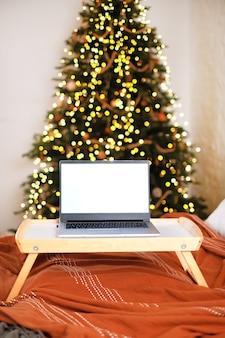 Laptop com caixa de presente e luzes de natal