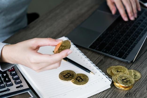 Laptop com calculadora e bitcoin dourado. conceito de investidores de criptomoeda.