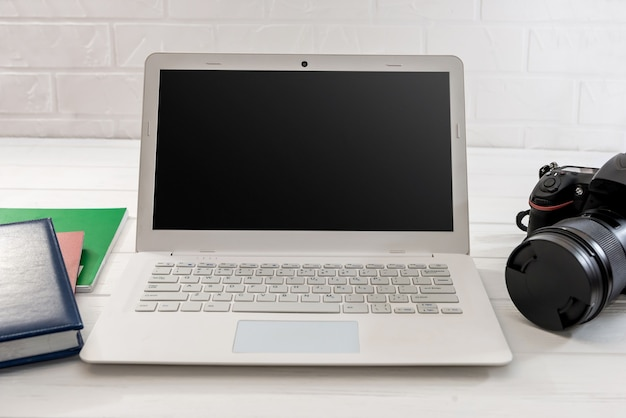 Laptop com calculadora e câmera digital na mesa