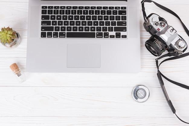 Laptop com câmera e bússola na mesa