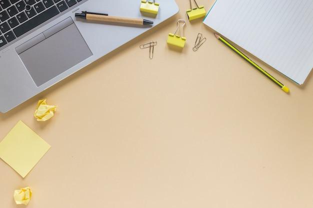Laptop com caneta; lápis; clipes de papel; notas auto-adesivas e bloco de notas em espiral no fundo bege