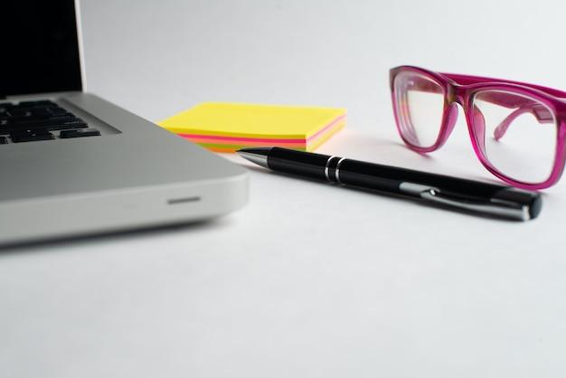 Laptop com caneta preta e blocos coloridos, óculos na mesa