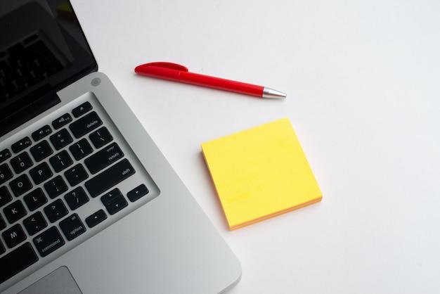 Laptop com caneta vermelha e blocos amarelos na mesa