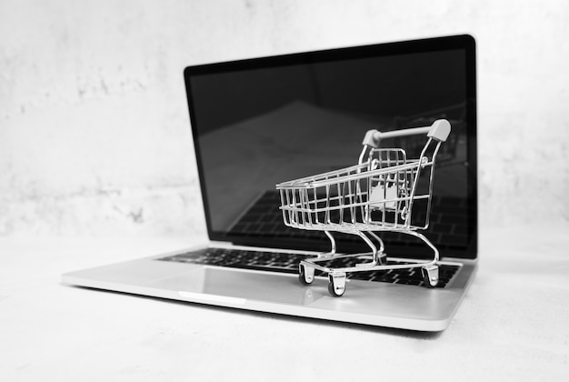 Laptop com carrinho de compras na parte superior