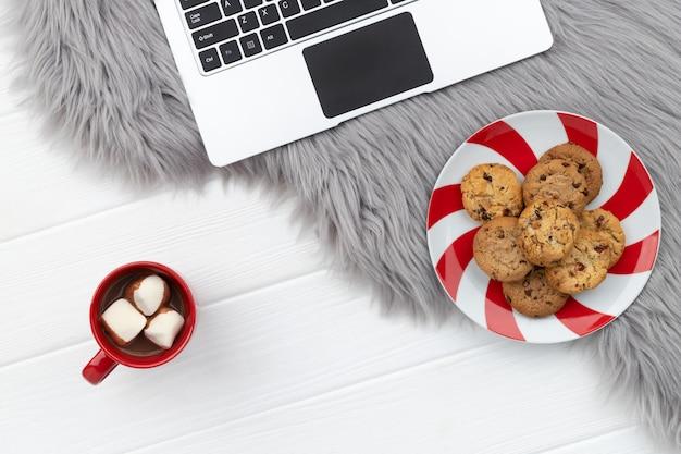 Laptop com chocolate e biscoitos em fundo peludo. compras online de natal trabalhando a partir do conceito de casa.