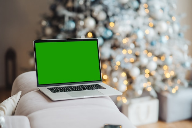 Laptop com chromakey de tela verde perto de decorações de ano novo tema de natal