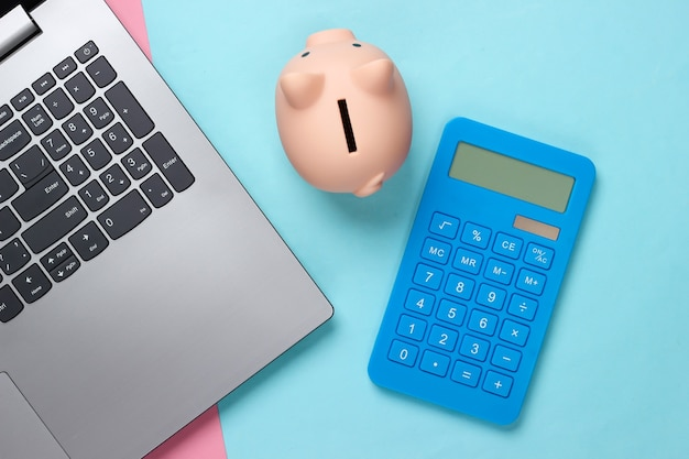 Laptop com cofrinho, calculadora em pastel azul rosa
