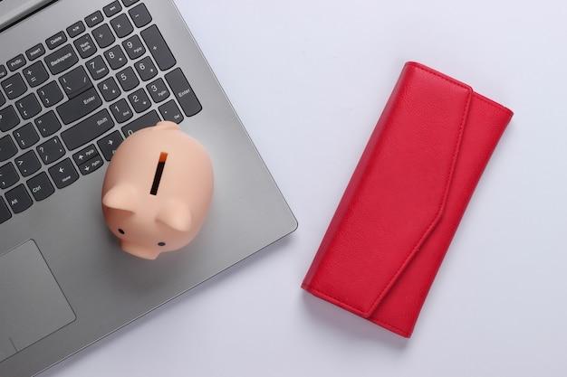 Laptop com cofrinho, carteira vermelha no branco