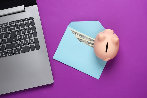 Laptop com cofrinho, envelope com dinheiro em roxo