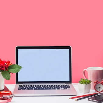 Laptop com copa e flores na mesa