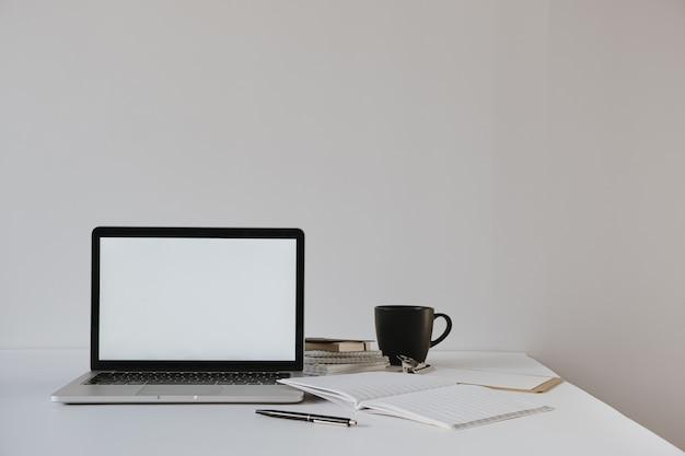 Laptop com cópia em branco na mesa com xícara de café, folha de papel, papelaria contra a parede branca