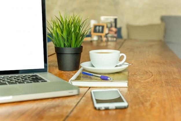 Laptop com copo de café e telefone celular na tabela de madeira no café.
