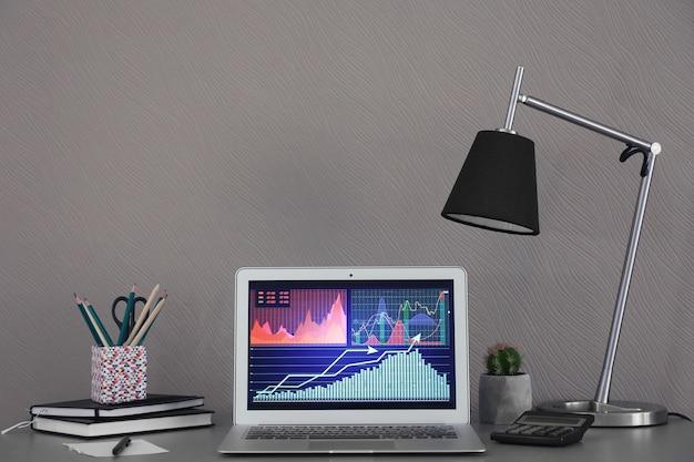 Laptop com dados de estoque na mesa dentro de casa