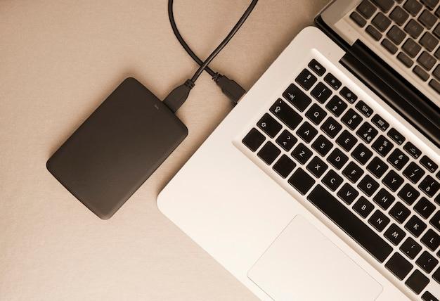 Laptop com disco rígido externo preto em vista de mesa de metal dourado