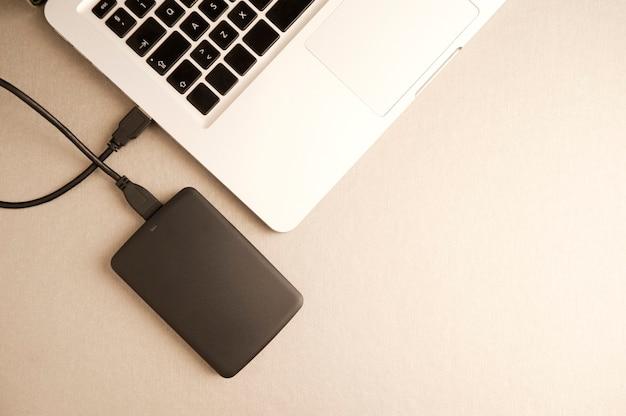 Laptop com disco rígido externo preto em vista superior da mesa de metal dourado