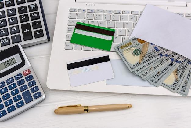Laptop com dólares em envelope e cartões de crédito