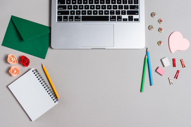 Laptop com envelope; bloco de notas em espiral; lápis e artigos de papelaria no contexto cinzento
