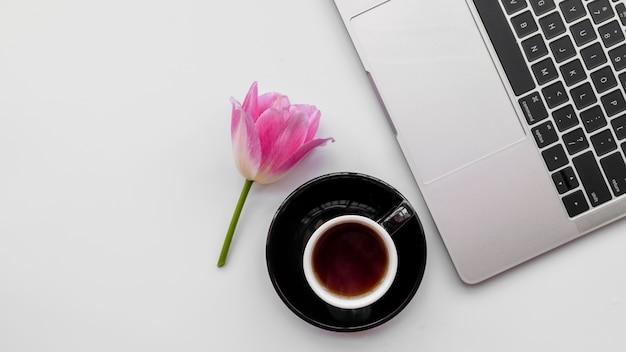 Laptop com flores e xícara de café