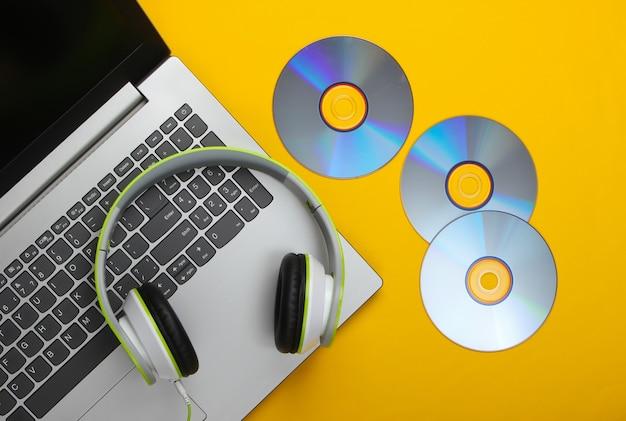 Laptop com fones de ouvido, discos de cd na superfície amarela