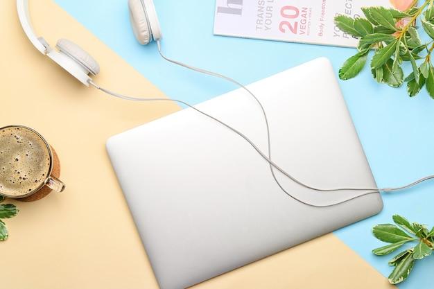 Laptop com fones de ouvido e uma xícara de café em azul e laranja, vista superior