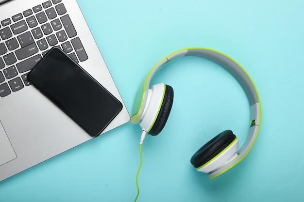 Laptop com fones de ouvido estéreo e smartphone na superfície azul