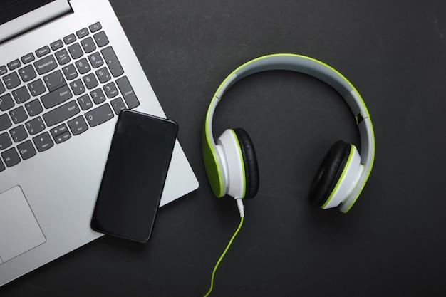 Laptop com fones de ouvido estéreo e smartphone na superfície preta