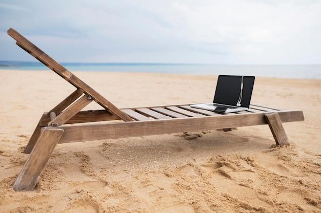 Laptop com fones de ouvido na cadeira de praia com areia