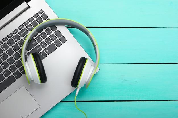 Laptop com fones de ouvido na superfície de madeira azul