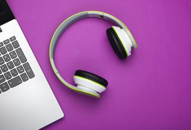 Laptop com fones de ouvido na superfície roxa