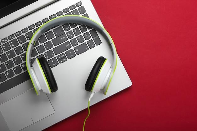 Laptop com fones de ouvido na superfície vermelha