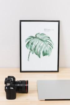 Laptop com foto e câmera na mesa de luz