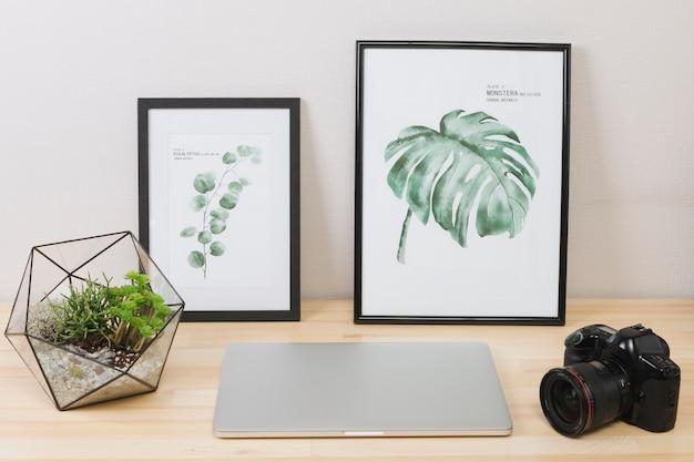 Laptop com fotos e câmera na mesa