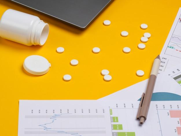 Laptop com frasco de comprimidos, gráficos e tabelas em um fundo amarelo. plano de negócios, análises financeiras, estatísticas médicas.