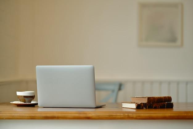 Laptop com material de escritório e gadgets na mesa de madeira