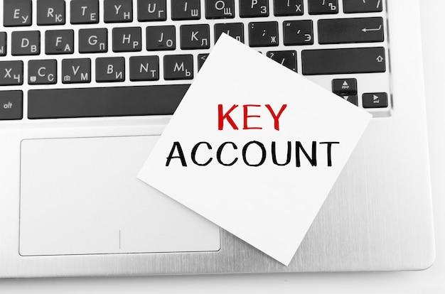 Laptop com memorando fura o teclado com o texto key account nele.