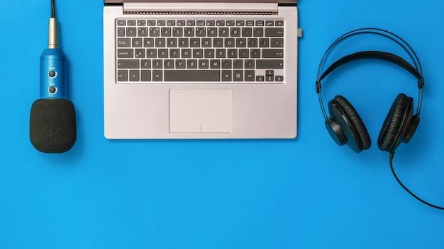 Laptop com microfone com fio e fones de ouvido pretos sobre fundo azul. o conceito de organização do local de trabalho. equipamentos para gravação, comunicação e escuta musical. postura plana.