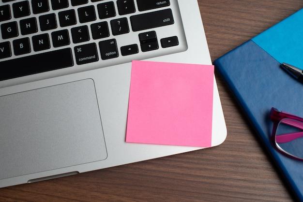 Laptop com nota rosa e caderno com caneta preta