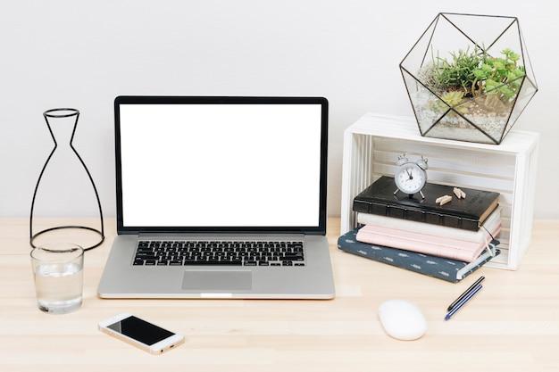 Laptop com notebooks na mesa de madeira clara
