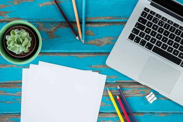 Laptop com papelaria e planta de maconha