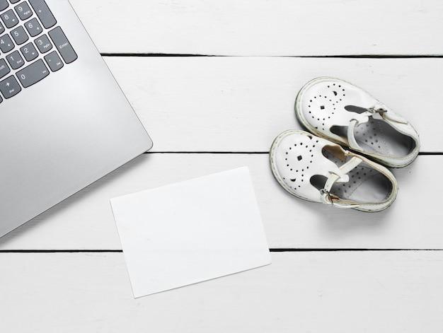 Laptop com pedaço de papel branco para espaço de cópia e sandálias infantis em madeira